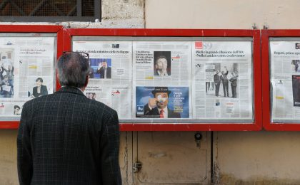 man reading newspaper in bulletin board