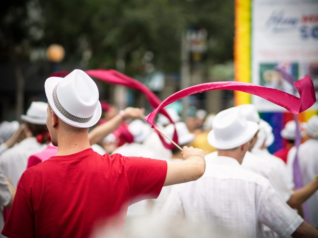 selective focus photography of man wearing pink t-shirt and white fedora hat holding pink ribbon with stick waving on the air during daytime
